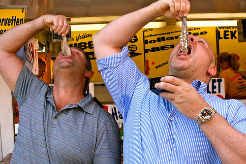 two men eating raw herrings